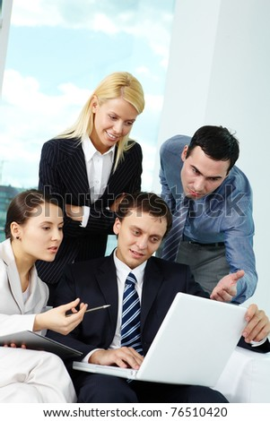 Portrait of several colleagues looking at laptop screen in office