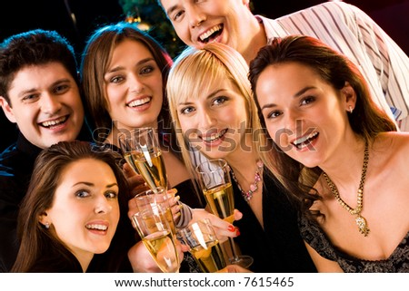 Portrait of several friends raising up their glasses