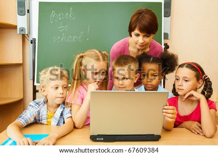 Portrait of several kids and their teacher looking at laptop screen by blackboard in classroom