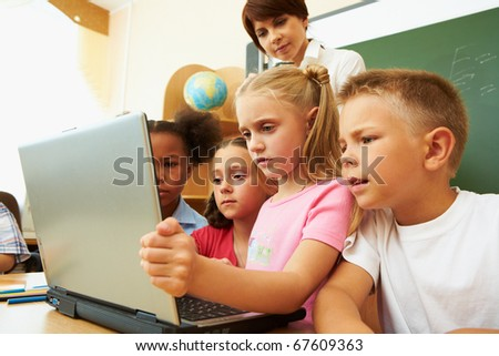 Portrait of several kids and their teacher looking at laptop screen in classroom - stock photo