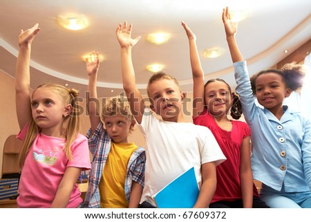 Portrait of several kids raising arms during lesson in classroom