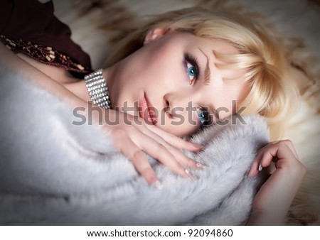 portrait of sexual blond woman dressed in fur and lingerie lying