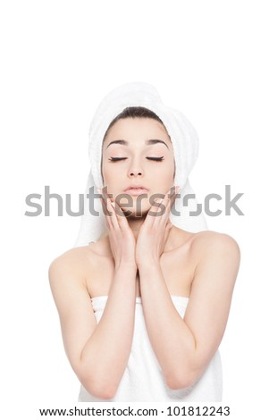 portrait of sexy beautiful young woman wrapped in towel body and head hold hand apply cream on face, isolated over white background concept of natural beauty care skin, hair, spa bath closed eyes
