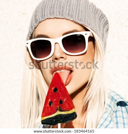 Portrait of sexy blond girl in white sunglasses and beanie hat licking watermelon lollipop with tongue