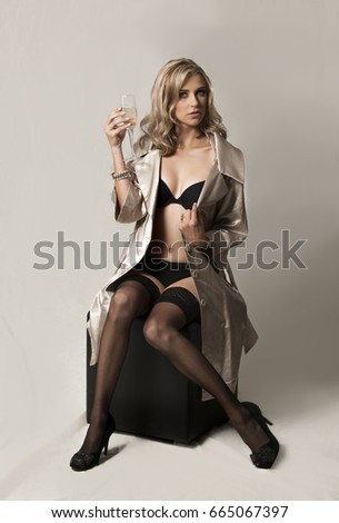 Portrait of sexy blonde woman wearing black lingerie, black stalkings and heels, with a gold colored jacket, seated on a black chair with a glass of champagne in her hand. #665067397