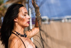 Portrait of sexy brunette with closed eyes and tattoos wearing stylish black necklace posing next to the net. Smokey eyes and dark lips. Shadows on her face. Fashion photoshooting on the beach.