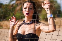 Portrait of sexy brunette with tattoos wearing stylish black massive necklace posing behind the net. Smokey eyes and dark lips. Shadows on her face. Fashion photoshooting on the beach.