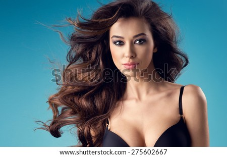 portrait of sexy brunette woman with a perfect body and large breasts posing in black lingerie on a blue studio background