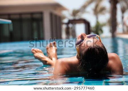 Portrait of sexy cheerful woman relaxing at the luxury poolside.  Girl at travel spa resort pool. Summer luxury vacation.  #295777460