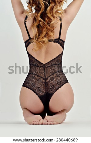 Portrait of sexy fashion model girl isolated on white background. Beautiful lady in elegant black bodysuit. Beauty brunette woman with attractive buttocks in lace lingerie. Female ass in underwear