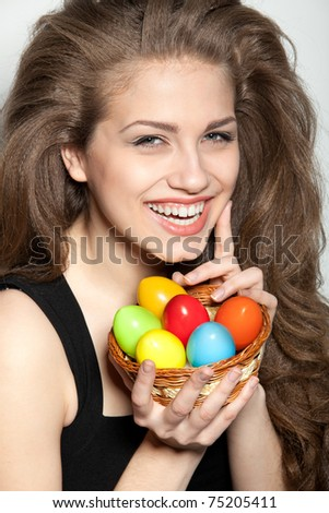 Portrait of sexy fashion model holding basket with Easter eggs