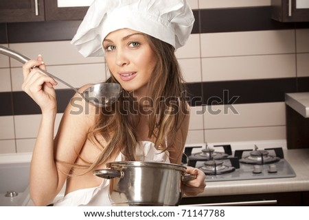 stock photo : Portrait of sexy housewife tasting dish in kitchen room