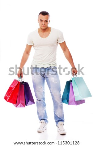Portrait of sexy man posing in studio with shopping bags