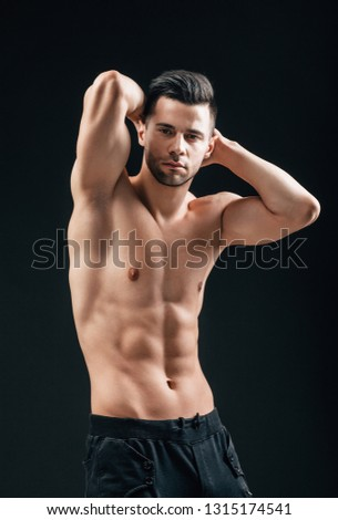 Portrait of sexy muscular shirtless man posing on black background