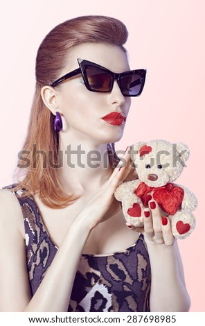 Portrait of Sexy redhead woman in trendy mini dress holds loving teddy bear with red heart on pink background. Seductive lady in sunglasses, sensual lips. Provocative young girl in playful flirty mood