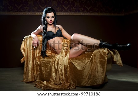 Portrait of sexy woman on the couch in studio