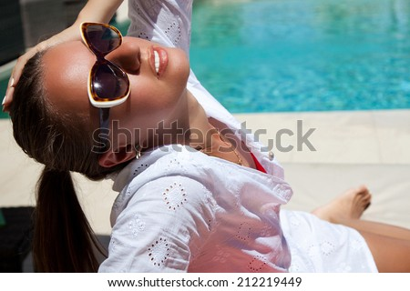 Portrait of sexy woman, relaxing at the luxury poolside. Girl at travel spa resort pool. Summer luxury vacation. (focus on woman face)