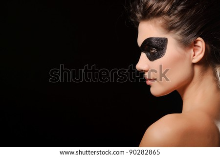 Portrait of sexy woman with black party mask on face, isolated on black