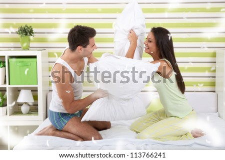 Portrait of sexy young couple having pillow fight in bedroom