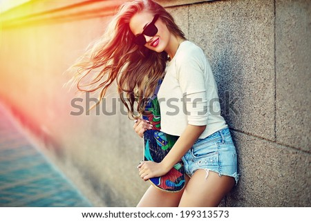 portrait of sexy young stylish smiling woman girl  model in bright modern cloth in glasses outdoors in the street in jean shorts with skateboard