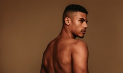 Portrait of shirtless muscular man looking away. Side view of african american man standing on brown background.