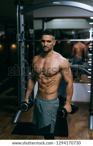Portrait of shirtless muscular man standing and holding dumbbells in hands.