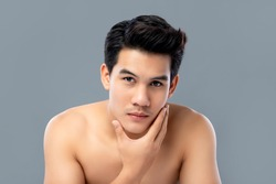 Portrait of shirtless young handsome Asian man for skincare and beauty concepts against gray studio background