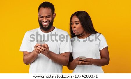 Portrait of shocked African American woman spying on her smiling boyfriend who using mobile phone, texting sms or scrolling social media news feed. Black couple standing over yellow studio background