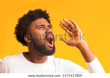 Portrait of shocked african guy screaming over orange background