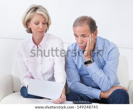 Portrait Of Shocked Couple Sitting On Couch Looking At Bill