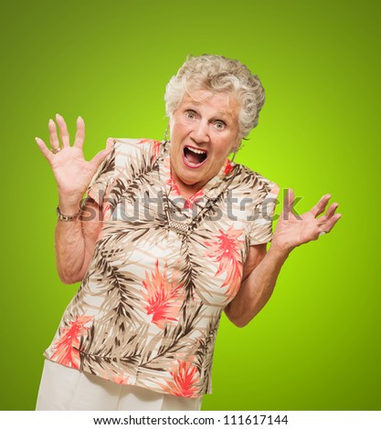 Portrait Of Shocked Elderly Woman Isolated Over Green Background
