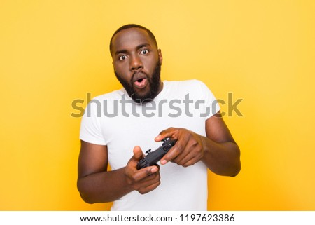 Portrait of shocked funny funky crazy man, playing online game, opened mouth, plump lips, isolated over bright vivid yellow background