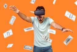 Portrait of shocked man wearing vr glasses, stretching hands forward, trying to get money, dollar rain falling, illusion of rich millionaire, playing virtual reality game, indoor studio shot