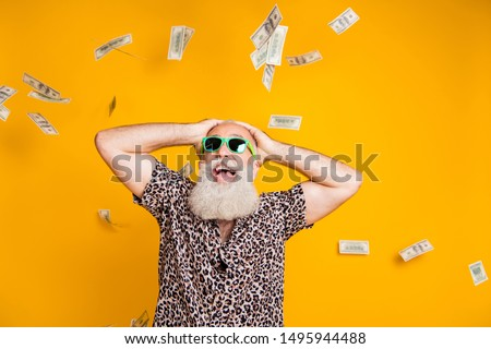Portrait of shocked retired old bearded funny funky man in eyewear eyeglasses scream wow omg win victory look at money falling wear leopard shirt isolated over yellow background