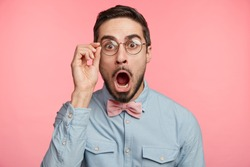 Portrait of shocked stupefied young bearded male model stares at camera as forgets some importnat information, keeps mouth widely opened, dressed in elegant clothes, isolated over pink background