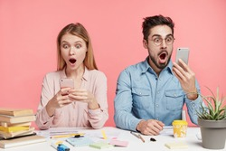 Portrait of shocked terrified male and female stare at mobile phones, type messages or read shocking news, sit next to each other at work place, isolated over pink background. Suprised students indoor