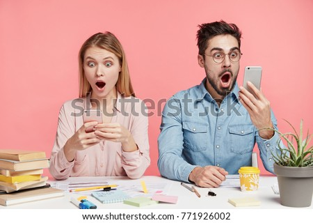 Portrait of shocked terrified male and female stare at mobile phones, type messages or read shocking news, sit next to each other at work place, isolated over pink background. Suprised students indoor - Shutterstock ID 771926002