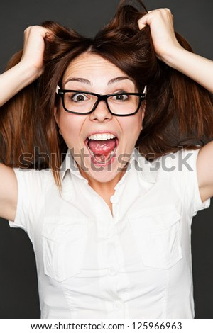 portrait of shocked young woman over dark background