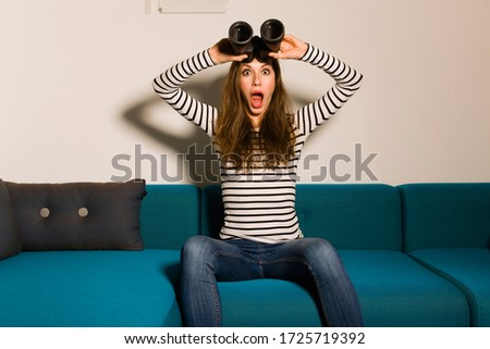 Portrait of shocked young woman sitting on couch with binoculars