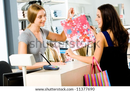 Portrait of shop assistant giving  bag to happy woman