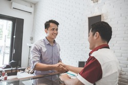 portrait of shop worker shaking hand of his client