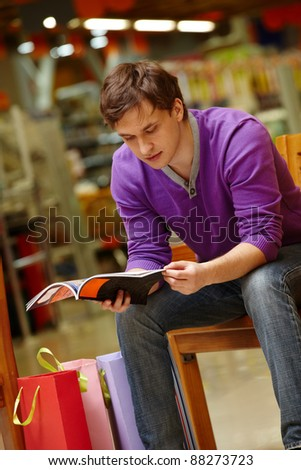 Portrait of shopper looking through magazine with paperbags near by