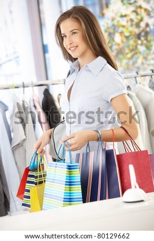Portrait of shopping girl standing in clothes store, holding shopping bags.?