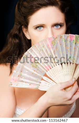 Portrait of shy mysterious beautiful young dancing girl holding bamboo fan in a depiction of a broadway dancer