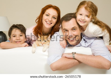 Portrait of siblings and their parents with cute cat looking at camera - stock photo