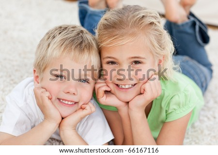 Portrait of siblings watching television on the floor in the living-room