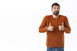 Portrait of silly and handsome smiling ordinary guy, bearded man show thumb-up and shrugging, smirk say not bad, encourage friend with average normal result, white background