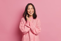 Portrait of sincere brunette Asian female model rubs palms and smiles broadly expresses happiness feels joyful has white even teeth wears oversized casual sweater isolated over pink background