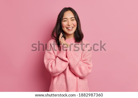 Portrait of sincere brunette Asian female model rubs palms and smiles broadly expresses happiness feels joyful has white even teeth wears oversized casual sweater isolated over pink background Stock photo ©