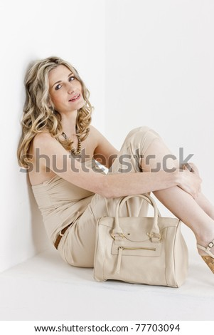portrait of sitting woman wearing summer clothes with a handbag